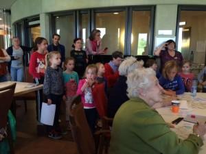 Jong & oud luisteren naar wethouder Coby Pennings tijdens creatieve/spel-middag in Polbeek